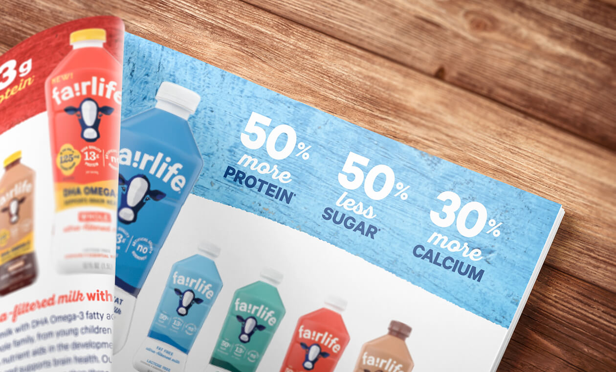 partial spread layout of the fairlife master brand brochure on a wood background focused on fairlife ultra filtered milk RTBs